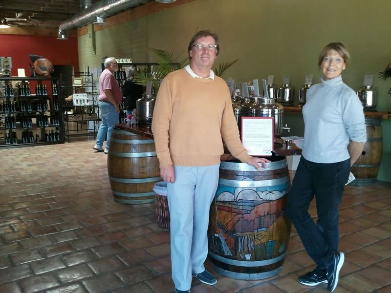 People pose next to a wine barrel
